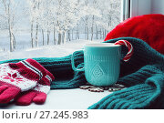 Купить «Winter background. Cup with candy cane, woolen scarf and red gloves on windowsill and winter forest outside. Still life with concept of spending winter time at cozy home», фото № 27245983, снято 28 ноября 2017 г. (c) Зезелина Марина / Фотобанк Лори