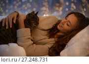 Купить «happy young woman with cat lying in bed at home», фото № 27248731, снято 15 октября 2016 г. (c) Syda Productions / Фотобанк Лори