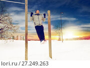 Купить «young man exercising on horizontal bar in winter», фото № 27249263, снято 10 ноября 2016 г. (c) Syda Productions / Фотобанк Лори