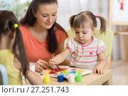 Купить «Children painting in preschool. Teacher helps by little girl.», фото № 27251743, снято 29 ноября 2017 г. (c) Оксана Кузьмина / Фотобанк Лори