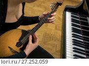 Купить «Девушка настраивает народный струнный щипковый музыкальный инструмент домра лежит у рояля в концертном зале», фото № 27252059, снято 29 ноября 2017 г. (c) Николай Винокуров / Фотобанк Лори