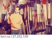 Купить «Smiling man choosing new pitchfork», фото № 27252139, снято 2 марта 2017 г. (c) Яков Филимонов / Фотобанк Лори