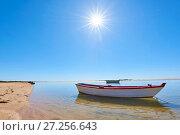 Купить «The sun shines above a small fishing boat on transparent lagoon water in Cacela Velha, Algarve, Portugal, Europe», фото № 27256643, снято 13 сентября 2017 г. (c) age Fotostock / Фотобанк Лори