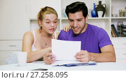Купить «Cheerful loving young couple looking at papers analyzing their finances at home», видеоролик № 27258095, снято 16 октября 2017 г. (c) Яков Филимонов / Фотобанк Лори