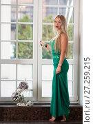 Купить «Девушка в зелёном платье стоит у створок окна», фото № 27259215, снято 28 октября 2017 г. (c) Литвяк Игорь / Фотобанк Лори