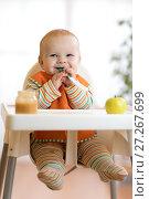 Купить «Cheerful baby child eats food itself with spoon. Portrait of happy kid boy in high-chair.», фото № 27267699, снято 24 ноября 2017 г. (c) Оксана Кузьмина / Фотобанк Лори