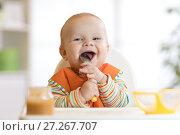 Купить «Cheerful baby child eats food itself with spoon. Portrait of happy kid boy in high-chair.», фото № 27267707, снято 24 ноября 2017 г. (c) Оксана Кузьмина / Фотобанк Лори