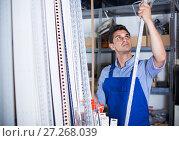 Купить «Sellerman is choosing ceiling», фото № 27268039, снято 26 июля 2017 г. (c) Яков Филимонов / Фотобанк Лори