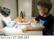 Купить «Мальчик 5 лет рисует красками новогодний рисунок при свете настольной лампы», фото № 27268283, снято 5 декабря 2017 г. (c) Юлия Юриева / Фотобанк Лори