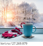 Купить «Winter background. Cup with candy cane on windowsill and winter trees outdoors», фото № 27269879, снято 28 ноября 2017 г. (c) Зезелина Марина / Фотобанк Лори