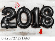 Купить «Bright metallic black balloons figures 2018, Christmas, New Year Balloon with glitter stars on white wood table background», фото № 27271663, снято 19 ноября 2017 г. (c) Сергей Тимофеев / Фотобанк Лори