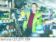 Купить «Customer woman in skiing equipment is choosing boots for skiing», фото № 27277199, снято 31 июля 2017 г. (c) Яков Филимонов / Фотобанк Лори