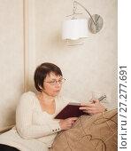 Купить «Пожилая женщина в очках читает книгу сидя на диване под лампой», фото № 27277691, снято 10 декабря 2017 г. (c) Юлия Бабкина / Фотобанк Лори