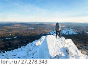 The mountaineer climbed the mountain top, man hiker standing at the peak of rock covered with ice and snow, view from back. Winter season. Стоковое фото, фотограф Сергей Дорошенко / Фотобанк Лори