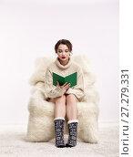 Купить «Brunette woman on furry arm-chair with book in hands», фото № 27279331, снято 8 октября 2017 г. (c) Serg Zastavkin / Фотобанк Лори