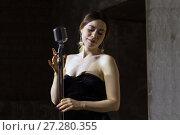 Купить «Красивая певица с ретро микрофоном на черном фоне», фото № 27280355, снято 2 декабря 2017 г. (c) Евгений Ткачёв / Фотобанк Лори