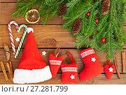 Купить «Рождественский натюрморт из зеленых еловых веток, красных сувениров ручной работы, леденцов и палочек корицы на деревянном фоне», фото № 27281799, снято 10 декабря 2017 г. (c) Виктория Катьянова / Фотобанк Лори