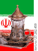 Купить «Iranian tea set. Teacup with traditional arabic ornaments on the background of the Iranian flag», фото № 27282459, снято 27 декабря 2015 г. (c) Евгений Ткачёв / Фотобанк Лори