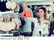 Купить «Female shopper examining bras in underwear shop», фото № 27282775, снято 20 марта 2017 г. (c) Яков Филимонов / Фотобанк Лори