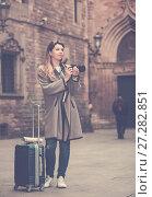 Купить «Young woman looking curious and taking pictures», фото № 27282851, снято 27 марта 2017 г. (c) Яков Филимонов / Фотобанк Лори