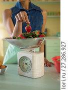 Купить «Young woman weighing strawberries on weighing machine in the kitchen», фото № 27286927, снято 17 августа 2017 г. (c) Wavebreak Media / Фотобанк Лори
