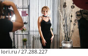 Stylish blonde woman in cocktail dress posing for photographer in clothing boutique. Стоковое видео, видеограф Константин Шишкин / Фотобанк Лори