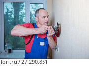 Купить «Male electrician connects the lamp on the wall», фото № 27290851, снято 21 мая 2017 г. (c) Наталья Давыдова / Фотобанк Лори