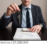 Купить «Мужчина держит в руке ключи от квартиры на фоне документов и денег. Фокус на ключах», эксклюзивное фото № 27290931, снято 6 ноября 2017 г. (c) Игорь Низов / Фотобанк Лори