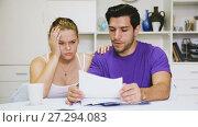 Купить «Young couple discussing serious financial situation at home», видеоролик № 27294083, снято 16 октября 2017 г. (c) Яков Филимонов / Фотобанк Лори