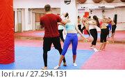 Купить «Group women are doing kick with coach in sporty gym.», видеоролик № 27294131, снято 22 октября 2017 г. (c) Яков Филимонов / Фотобанк Лори