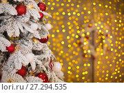 Купить «Snowy Christmas tree with red gifts decoration before bokeh yellow lights on the wall in holiday room interior home», фото № 27294535, снято 17 июля 2019 г. (c) Photobeauty / Фотобанк Лори