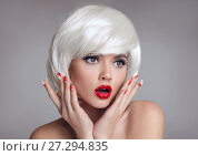 Купить «Shocked face. Blond Woman with red lips and manicure nails surprise holds cheeks by hand. Beautiful girl with white short bob hairstyle isolated on gray background. Expressive facial expressions.», фото № 27294835, снято 6 декабря 2017 г. (c) Photobeauty / Фотобанк Лори