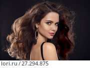 Fashion portrait of gorgeous sexy brunette woman with long healthy hair style and evening makeup, black earrings jewelry looking at camera isolated on black studio background with back light. Стоковое фото, фотограф Photobeauty / Фотобанк Лори