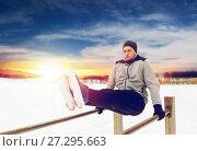 Купить «young man exercising on parallel bars in winter», фото № 27295663, снято 10 ноября 2016 г. (c) Syda Productions / Фотобанк Лори