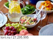 Купить «vegetable salad in bowl and other food on table», фото № 27295995, снято 5 октября 2017 г. (c) Syda Productions / Фотобанк Лори