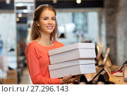 Купить «woman or shop assistant with shoe boxes at store», фото № 27296143, снято 22 сентября 2017 г. (c) Syda Productions / Фотобанк Лори