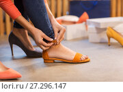 Купить «young woman trying sandals at shoe store», фото № 27296147, снято 22 сентября 2017 г. (c) Syda Productions / Фотобанк Лори
