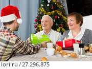 Купить «Family gives Christmas gifts», фото № 27296875, снято 19 марта 2019 г. (c) Яков Филимонов / Фотобанк Лори