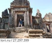 Купить «The man the tourist on the steps of the ancient destroyed temple. Siem Reap, Cambodia», фото № 27297399, снято 1 февраля 2015 г. (c) Куликов Константин / Фотобанк Лори