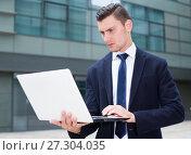 Купить «Businessman is examinating project on laptop», фото № 27304035, снято 3 июня 2017 г. (c) Яков Филимонов / Фотобанк Лори