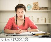 Купить «Girl doing homework», фото № 27304135, снято 29 марта 2017 г. (c) Яков Филимонов / Фотобанк Лори