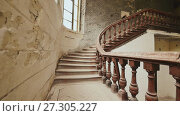 A staircase with wooden railing in an abandoned architectural building. The legacy of past architectural times. Handrail stairs made of dark wood. Shooting in motion with electronic stabilization. Стоковое видео, видеограф Mikhail Davidovich / Фотобанк Лори