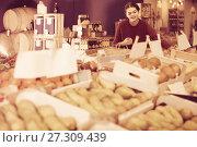 Купить «Portrait of young customer selecting apple in grocery», фото № 27309439, снято 1 марта 2017 г. (c) Яков Филимонов / Фотобанк Лори