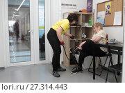 Купить «Инструктор помогает надеть манжеты на ноги пациенту в центре Бубновского», эксклюзивное фото № 27314443, снято 22 декабря 2017 г. (c) Дмитрий Нейман / Фотобанк Лори
