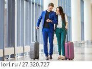 Купить «Tourists couple with baggage in international airport. Man and woman going on landing», фото № 27320727, снято 13 июля 2017 г. (c) Дмитрий Травников / Фотобанк Лори