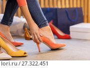 Купить «young woman trying high heeled shoes at store», фото № 27322451, снято 22 сентября 2017 г. (c) Syda Productions / Фотобанк Лори