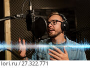 Купить «man with headphones singing at recording studio», фото № 27322771, снято 18 августа 2016 г. (c) Syda Productions / Фотобанк Лори