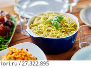 Купить «pasta with basil in bowl and other food on table», фото № 27322895, снято 5 октября 2017 г. (c) Syda Productions / Фотобанк Лори
