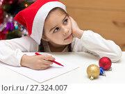 Купить «Симпатичная маленькая девочка в красном колпаке пишет письмо Деду Морозу и мечтательно смотрит в сторону», фото № 27324007, снято 19 декабря 2017 г. (c) Лариса Капусткина / Фотобанк Лори