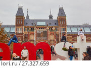 Tourists climbing on the I Amsterdam giant letters marketing slogan with Rijksmuseum behind, Museumplein (Museum Square), Amsterdam, Holland (2017 год). Редакционное фото, фотограф HelloWorld Images / age Fotostock / Фотобанк Лори